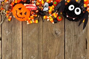 Halloween candy and decor top border against a rustic wood background